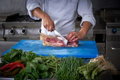 Chef hands cutting meat in restaurant kitchen Stock Photo