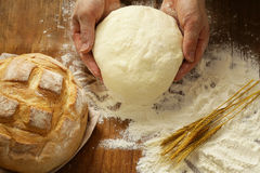 Chef hands with dough and homemade natural organic bread and flour Royalty Free Stock Photos