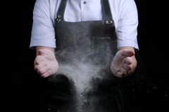 Chef hands in flour on black background. clap with flour. baking bread and and making pizza or pasta royalty free stock photo