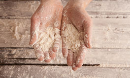 Chef hands with flour over a wooden table Royalty Free Stock Image