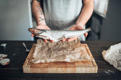 Chef hands holds raw fish over cutting board. Male chef hands holds raw fish over wooden cutting board. Seafood cooking. Fresh sea food Royalty Free Stock Photo
