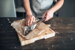 Chef hands with knife cut up fish on cutting board Stock Photo