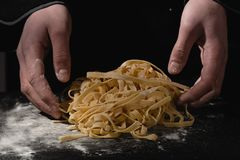 Chef hands making spaghetti, pasta, noodles with fresh pasta on black table with stock photos