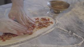 Chef hands making turkish arab food fatayer in modern restaurant kitchen close up. Man puts roasted meat with vegetables. On the dough preparing it for baking stock video