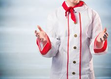 Chef with hands out against blurry blue wood panel Stock Images