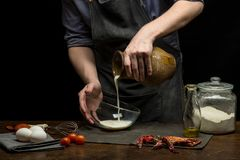 Chef hands are pouring milk from terracotta jar to prepare dough. Black background stock photos