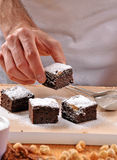 Chef hands preparing and slicing fresh  brownies Stock Image