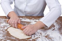 Chef hands roll the dough on floured  table Royalty Free Stock Image