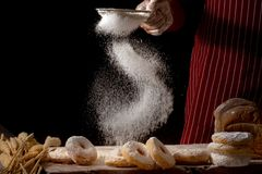 Chef hands sprinkling preparing bread dough and doughnuts with icing sugar on wooden table isolated on black background. Food concept royalty free stock photos