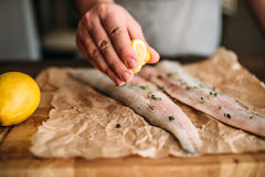 Chef hands squeeze lemon on raw fish closeup view Royalty Free Stock Photo