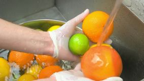 Chef hands washing oranges and lime, close up. Two oranges and lime washing under tap stock video footage