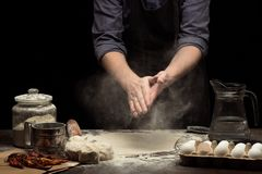 Chef hands are working with wheat flour to make a dough royalty free stock image