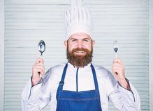 Chef happy smiling face hold spoon and fork. Man handsome with beard holds kitchenware on white background. Cooking stock photography