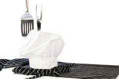 Chef Hat Apron Spatula Fork. A white chef hat, a black and white striped chefs apron, spatula and a fork on white background Royalty Free Stock Photography