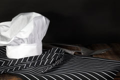 Chef Hat and Apron. A white chef hat, a black and white striped chefs apron, a spatula and a fork on wood surface and black background