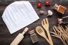 Chef hat with cooking utensils. And vegetables on wooden table royalty free stock photos