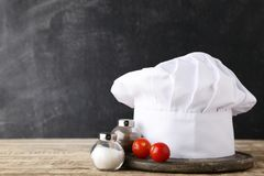 Chef hat with salt, pepper and tomato stock photography