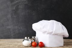 Chef hat with salt, pepper and tomatoes stock photos