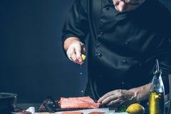 Chef haut étroit mettant le sel sur la tranche saumonée Le grand saumon est aux mains du cuisinier de chef Il utilise un couteau  images libres de droits