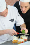 Chef helping young cook to preparing dessert Royalty Free Stock Images