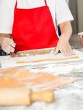 Chef heureux Rolling Pasta Sheet au compteur image stock