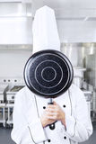 Chef behind pan at work Stock Images