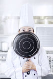 Chef hiding her face with a pan Royalty Free Stock Photos