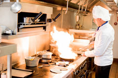Chef with high burning flames. Male chef cooking in a frying pan on a kitchen Stock Image