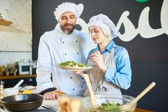Tasting the salad. Chef with his assistant tasting vegetable salad Stock Photos