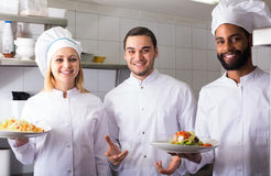 Chef and his assistants preparing meal. Russian chef and his assistants preparing meal in tavern stock photography