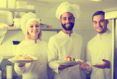 Chef and his assistants preparing meal. Smiling chef and his assistants preparing meal indoors stock photos