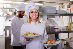 Chef and his assistants preparing meal. Smiling chef and his assistants preparing meal in kitchen indoors royalty free stock photos