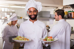 Chef and his assistants preparing meal. Smiling chef and his assistants preparing meal in tavern stock images