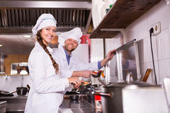 Chef and his helper at bistro kitchen Royalty Free Stock Image