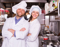 Chef and his helper at bistro kitchen Royalty Free Stock Photos