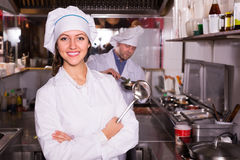 Chef and his helper at bistro kitchen Royalty Free Stock Images