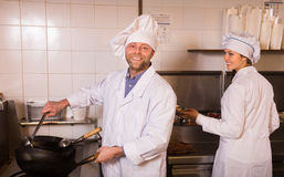 Chef and his helper at bistro kitchen Stock Photo