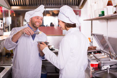 Chef and his helper at bistro kitchen. Two cheerful smiling cooks working at kitchen in take-away restaurant royalty free stock photos