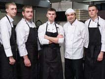 Chef restaurant teamwork professional staff. Chef and his team of professional staff at restaurant. Teamwork brings success to any business stock photography