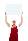 Chef holding advertising board over her head Royalty Free Stock Image
