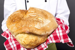 Chef holding a big rustic bread Royalty Free Stock Photography