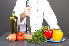 Chef holding a big sharp knife on a board ready to cook. Over gray background Stock Photos