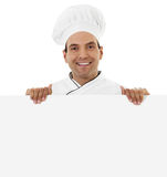 Chef holding a blank sign. Stock image of a cheerful male chef holding a blank sign isolated on white Royalty Free Stock Image