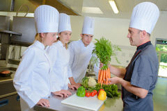 Chef holding bunch carrots before trainees Stock Images
