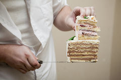 Chef holding cake cuttings. Nice wedding cake with cream and flower decorations. Chocolate and strawberry filling Royalty Free Stock Photos