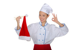 Chef holding chopsticks cap of Santa Claus Stock Photo