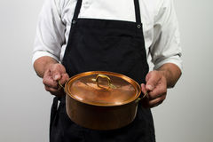 Chef holding copper pan Stock Photos