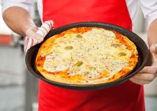 Chef Holding Delicious Pizza In Pan Royalty Free Stock Image