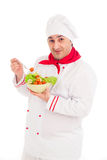 Chef  holding dish with salad and fresh vegetables  wearing red Royalty Free Stock Image