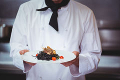 Chef holding a dish with spaghetti. In commercial kitchen Royalty Free Stock Photos